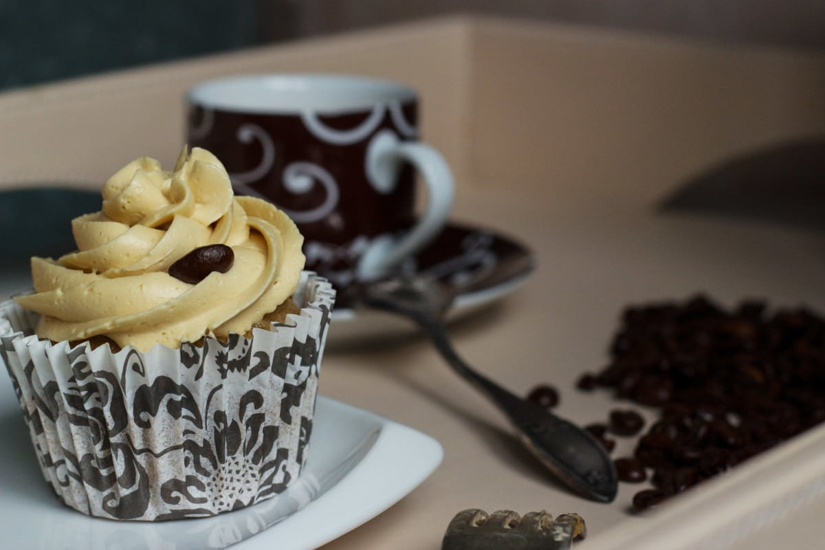 frosted cupcake with a coffee cup in the background