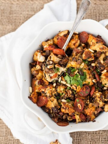 Top down of stuffing with serving spoon in white dish