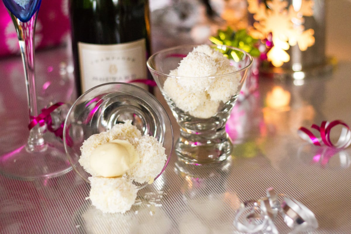 Side shot of white chocolate truffles in small glasses in front of a bottle