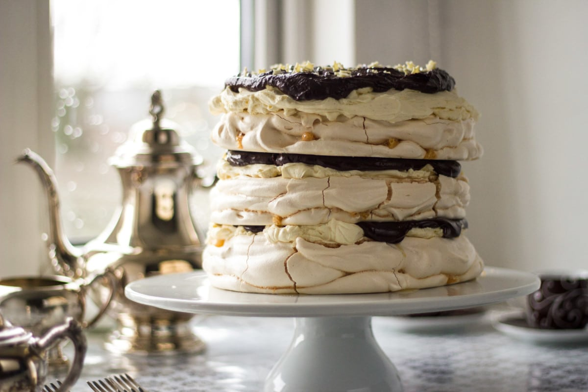 Side shot of meringue cake on stand with tea pot in background