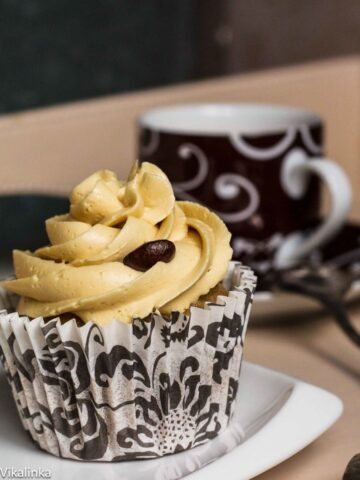 Close-up of a cupcake with coffee in the background