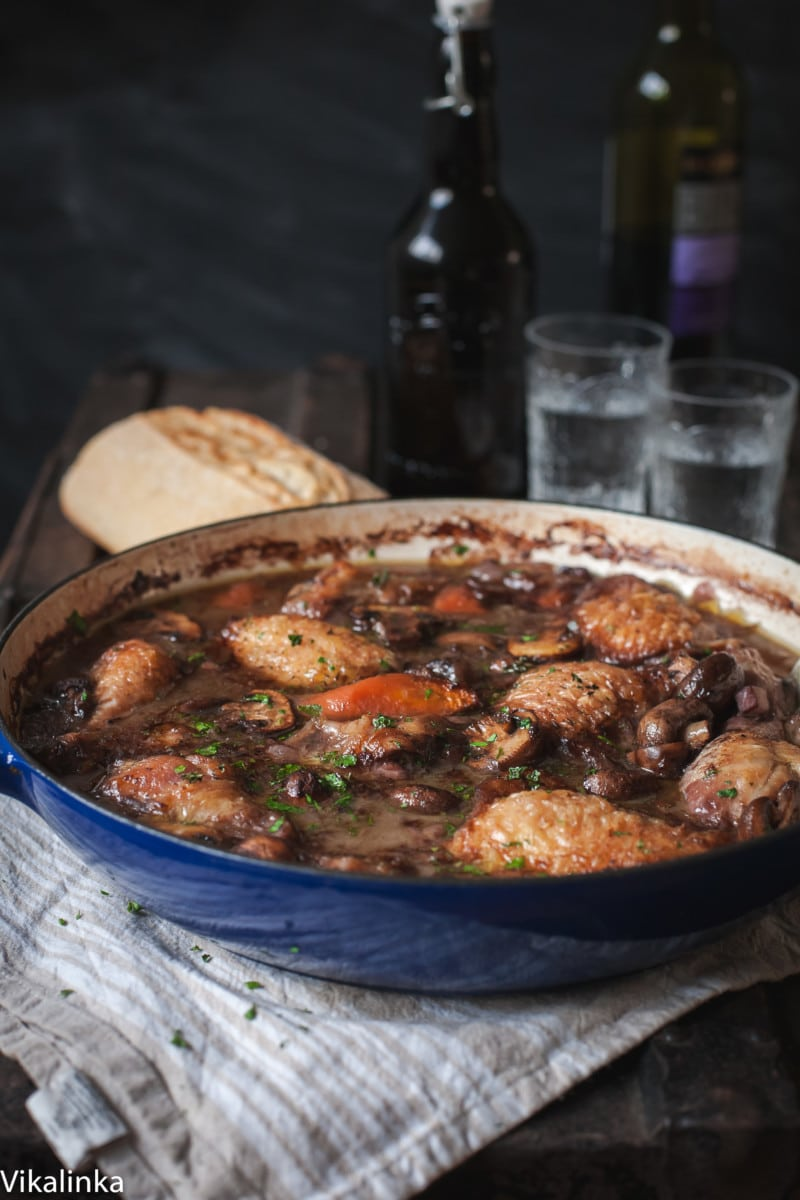 Chicken coq au vin with red wine and glasses in background