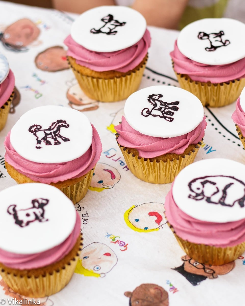 Top down view of pink icing cupcakes with animal designs