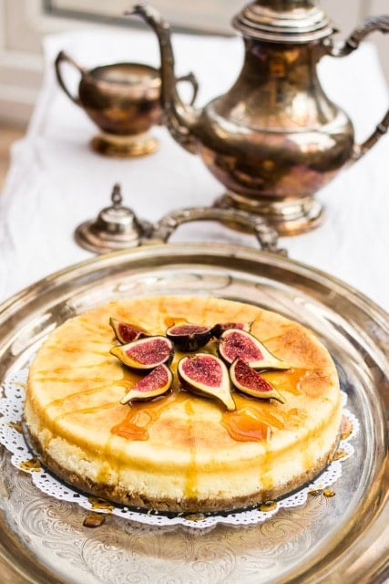 Top down view of vanilla cheesecake with figs on top, on a silver dish