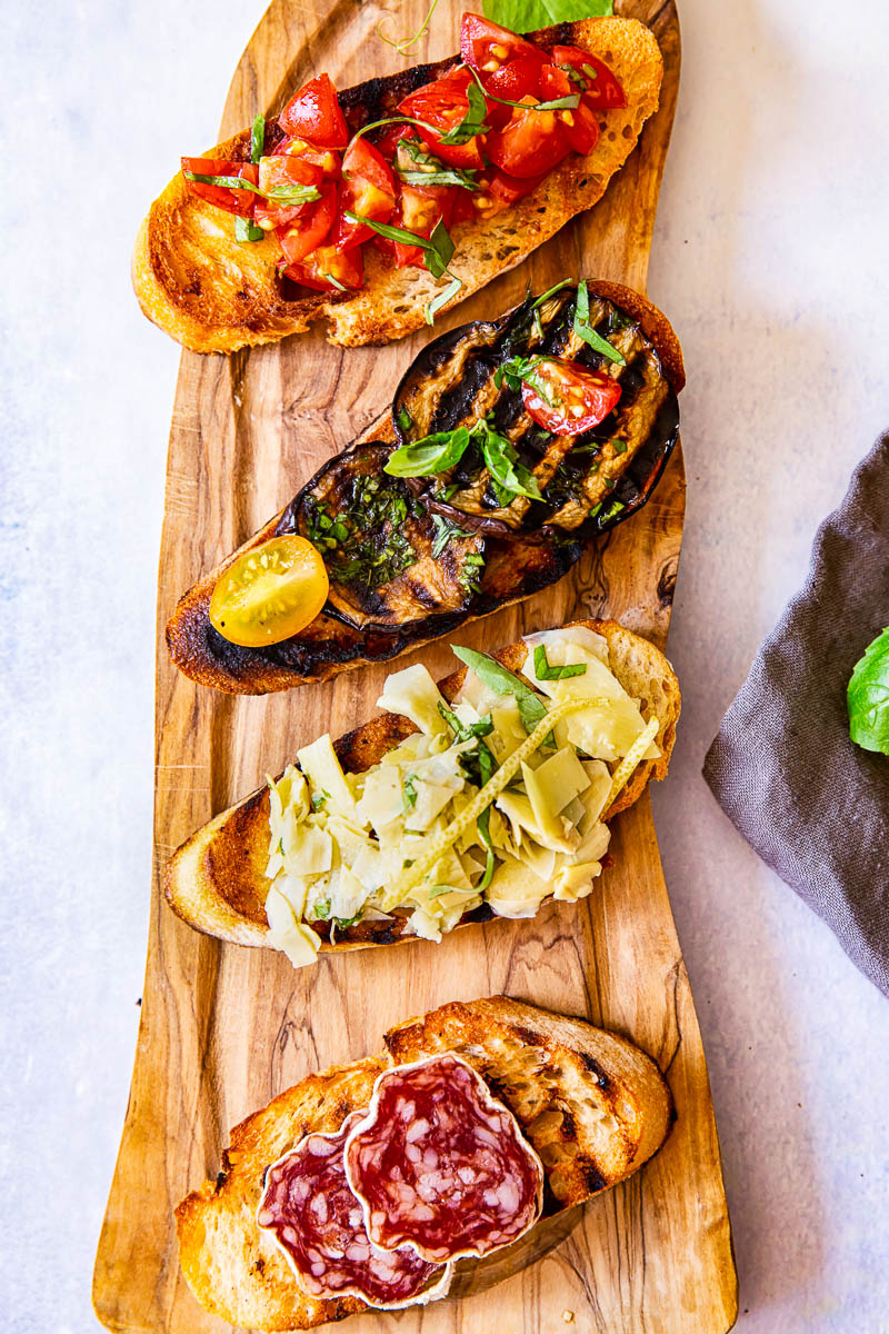 Four bruschetta slice with various toppings on wooden board.