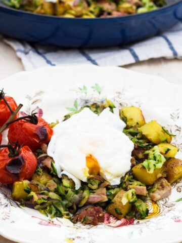 Zucchini and ham hash on white plate with cooked tomatoes