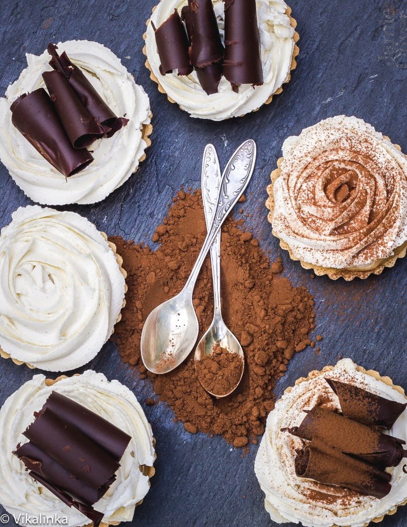 Top down of tarts in a circle with chocolate and spoons at the centre