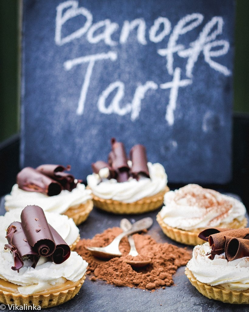 Side shot of banoffee tarts with chocolate powder in the middle on a blue surface