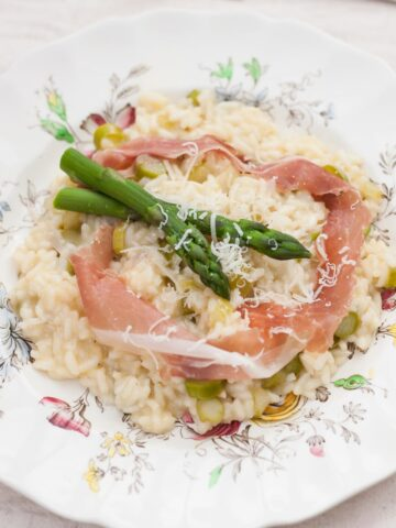 Top down of asparagus risotto on white surface