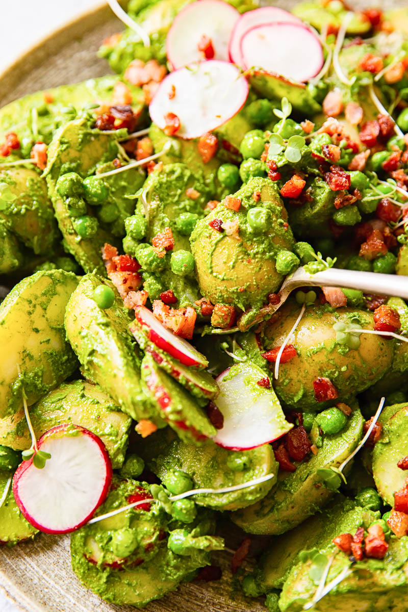 Pesto potato salad with sliced radishes, peas and bacon