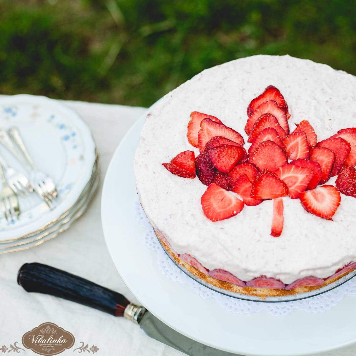 Top down of frasier torte with strawberries on top, on a white stand