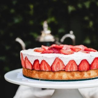 Side shot of cake with strawberries on side on a white stand
