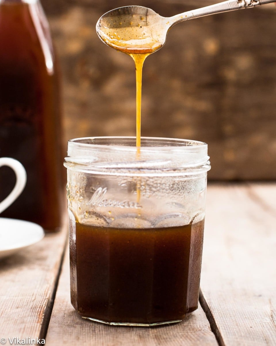 Spoon pouring pumpkin spice syrup into a jar