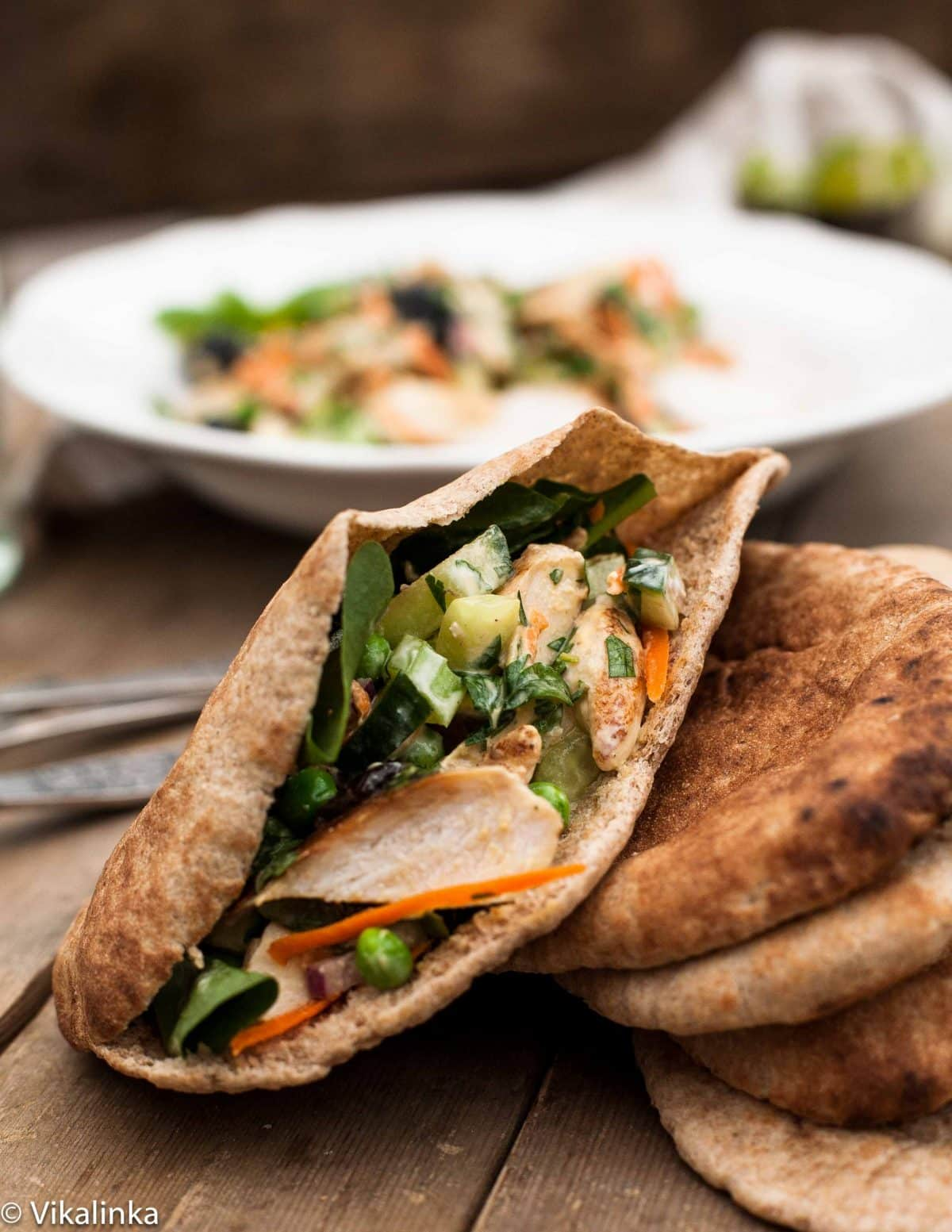 Chicken sald in pita bread with salad in background