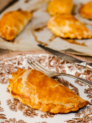 Cornish pasty on a white plate with brown design