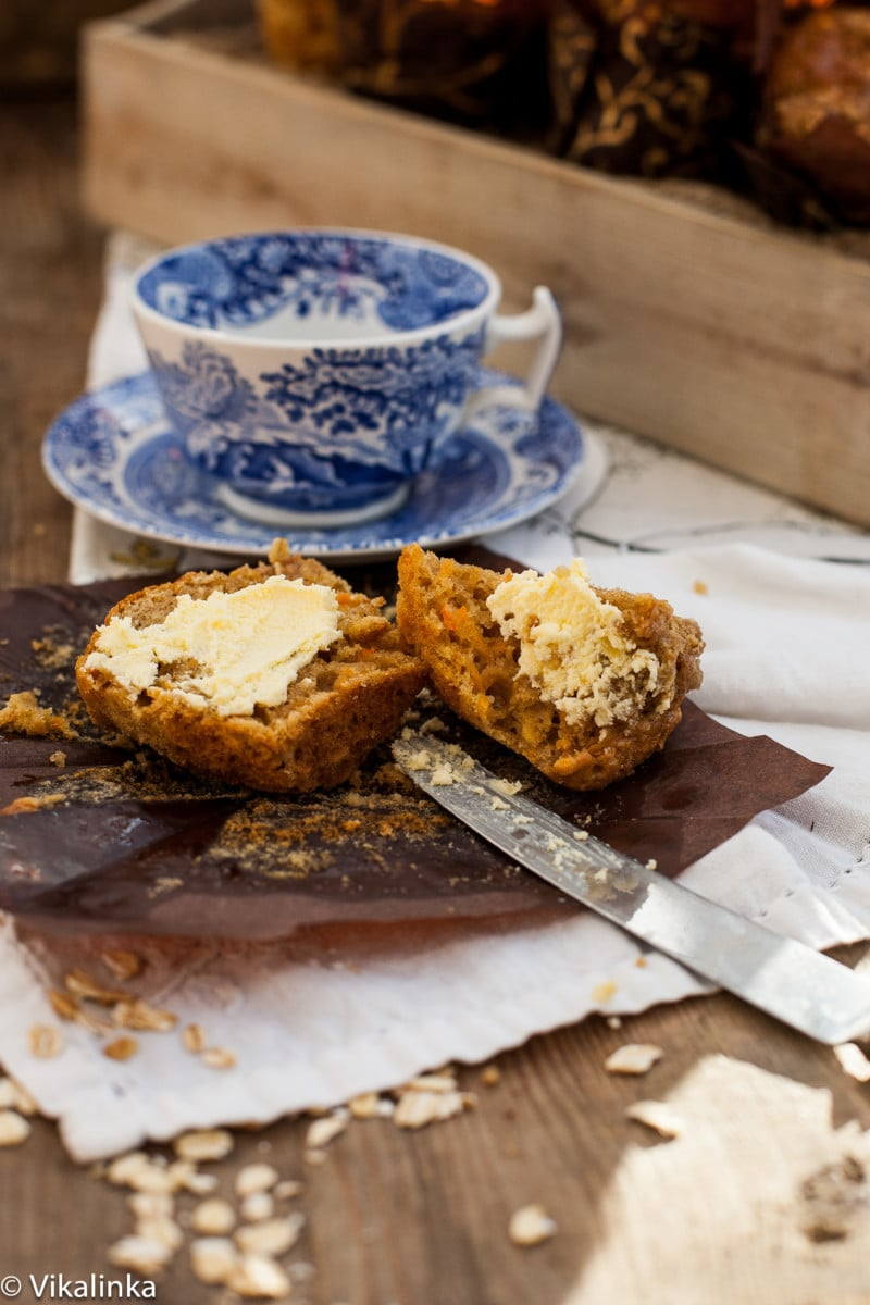 muffin cut in half and spread with butter, blue teacup in the background