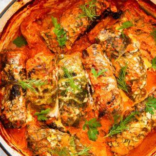 cabbage rolls in creamy tomato sauce in orange pot