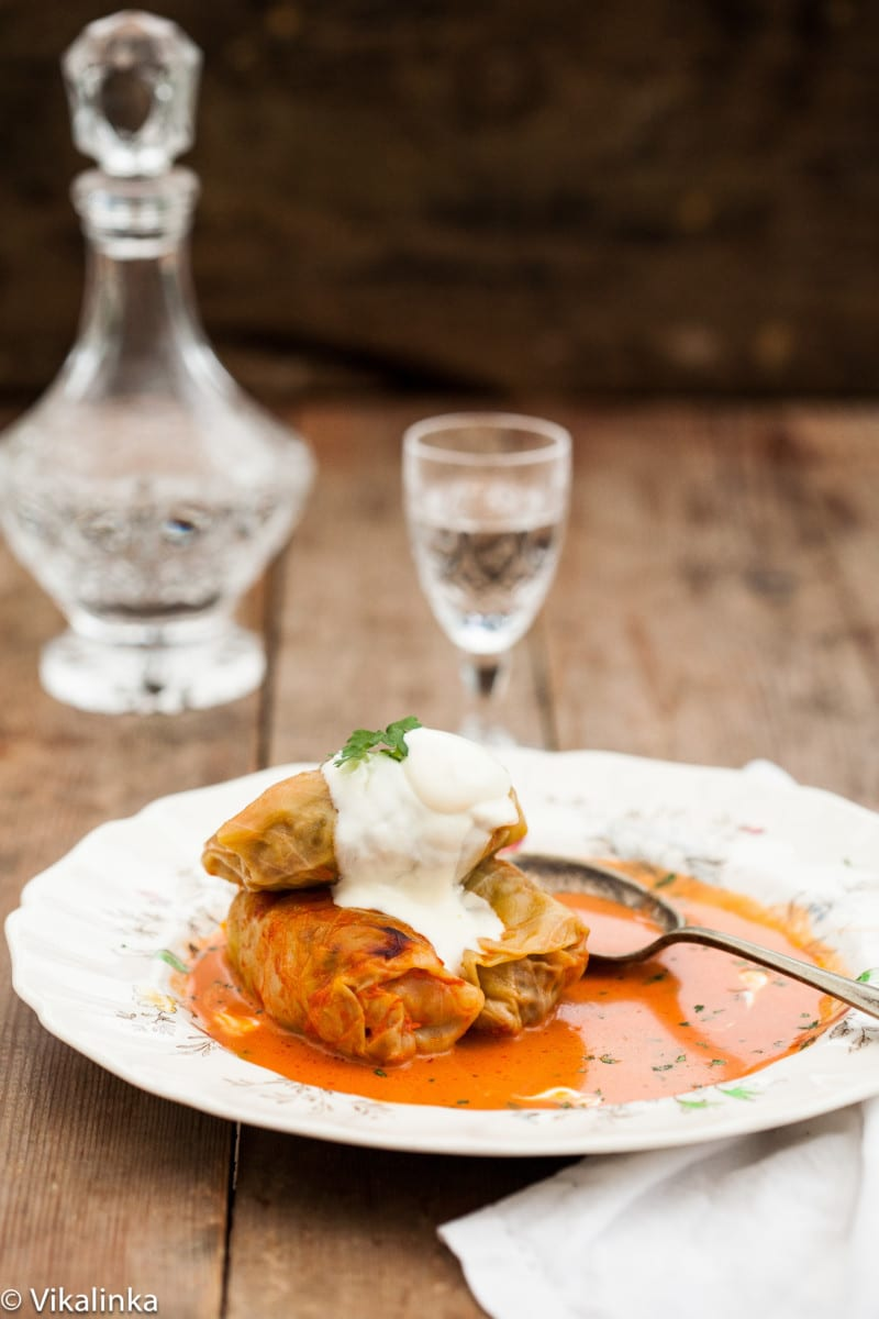 three cabbage rolls in sauce on a plate, decanter with clear liquid in the background