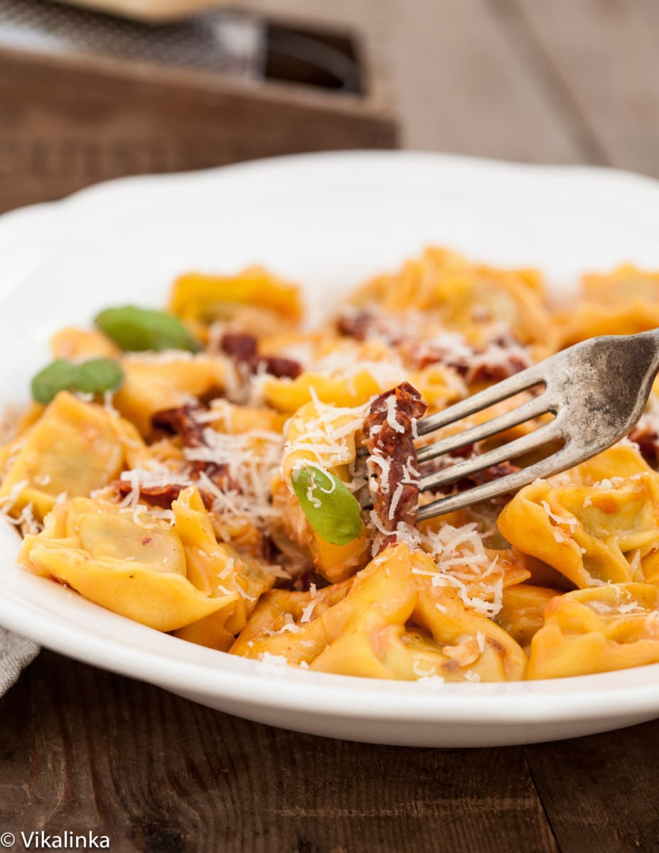 A bowl with tortellini and sun-dried tomatoes, a fork