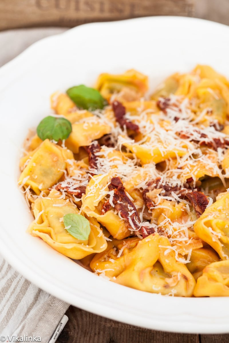 tortellini with orange sauce and sun-dried tomatoes in a white bowl