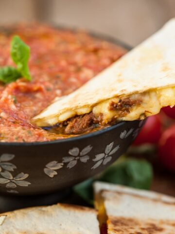 quesadilla being dipped in salsa