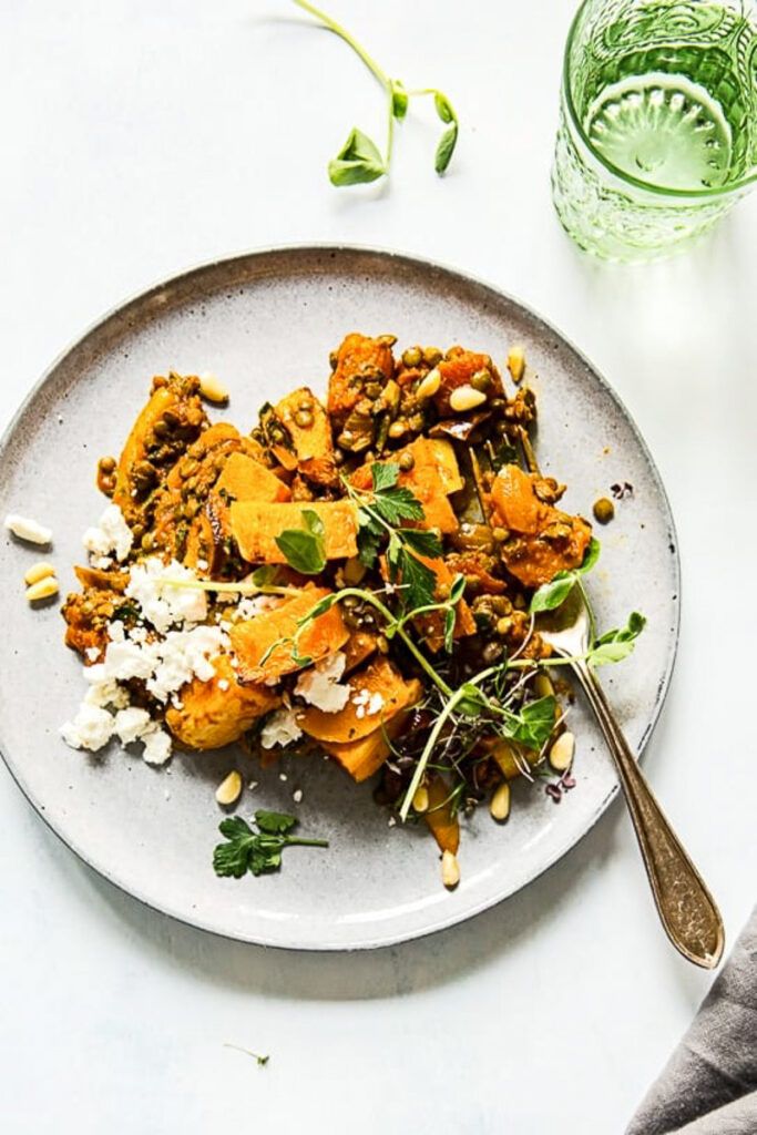 top down view of roasted squash, lentils and feta on grey plate