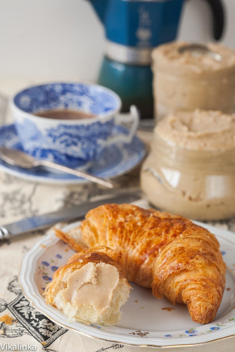cashew butter on a croissant, a cup of coffee and a jar of cashew butter in the background