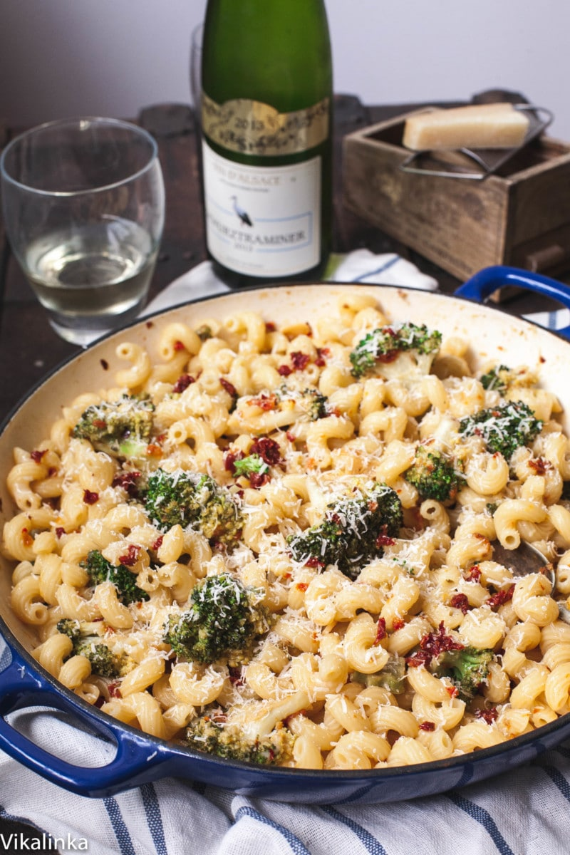 pasta with broccoli in a blue pan, a bottle of wine, glasses and Parmesan cheese in the background.