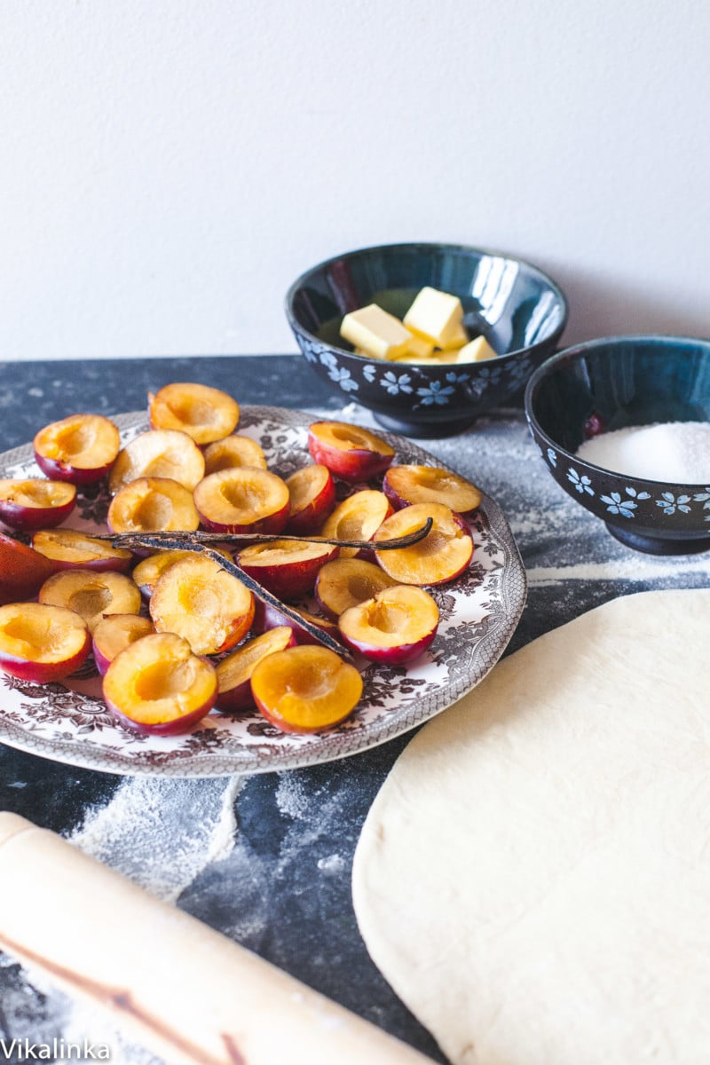 plums cut in half on plate, puff pastry rolled out and bowl of sugar and cubed butter