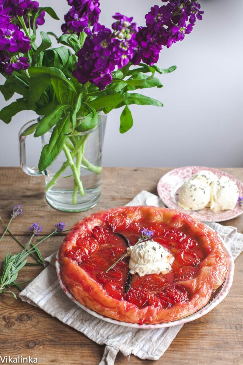 Plum Tarte Tatin topped with lavender cream and a vase with purple flowers in the background