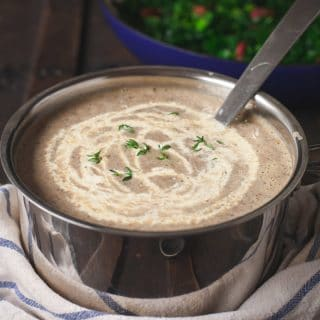 Mushroom soup in a pot with cream drizzled on top of it.