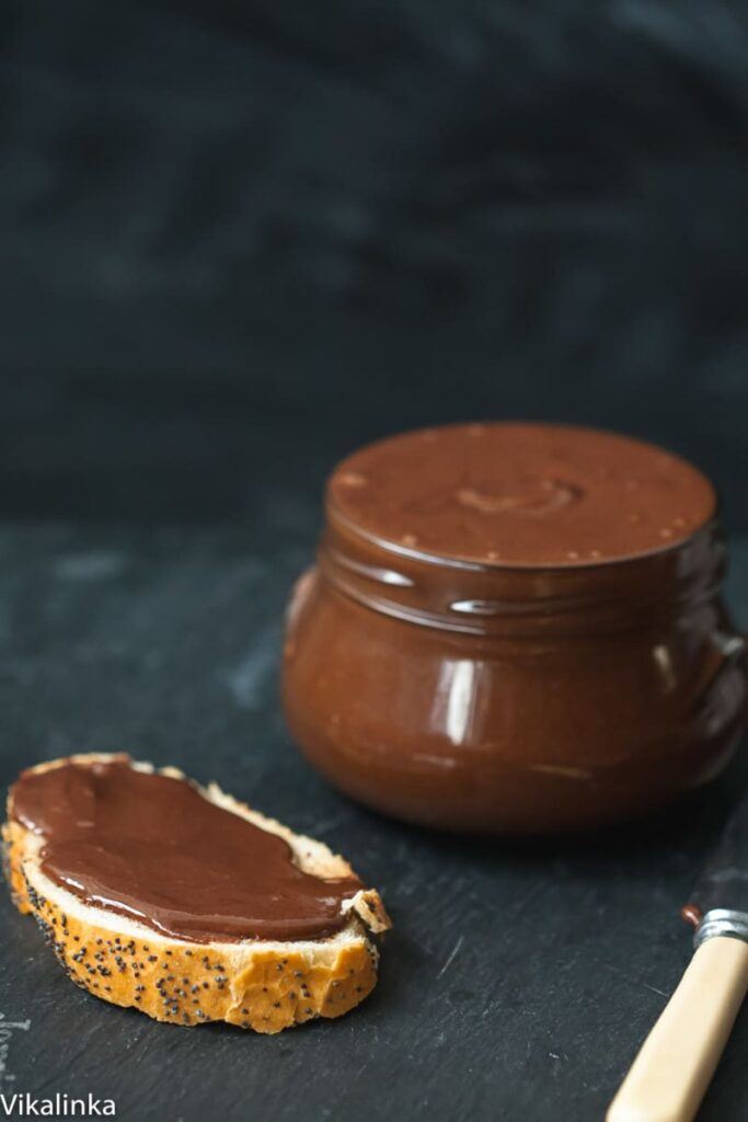 Close up of nutella on bread next to jar