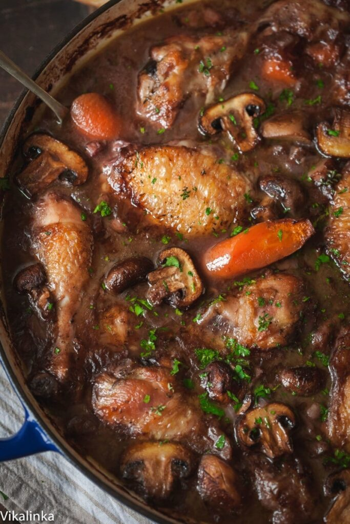 top down view of coq au vin with carrots and mushrooms