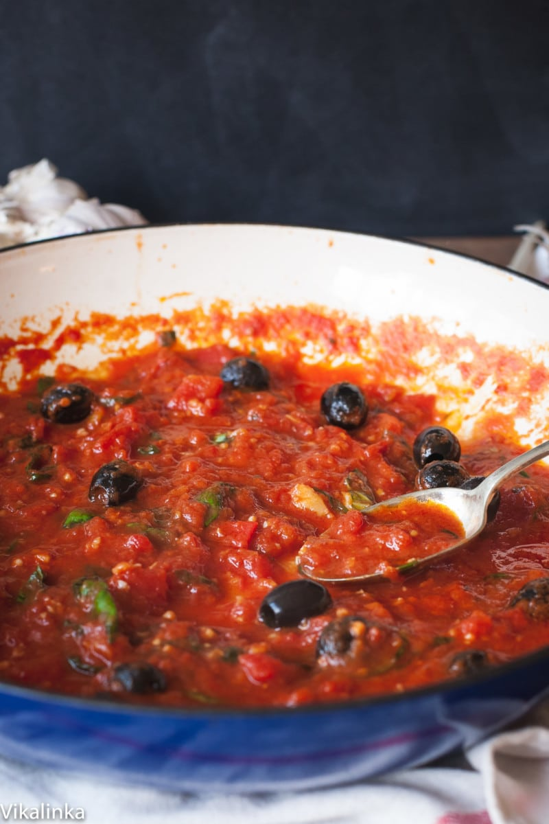 tomato sauce with black olives in a blue pan