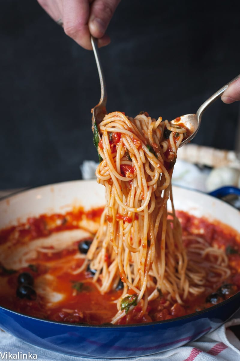spaghetti with tomato sauce being tossed in a blue pan