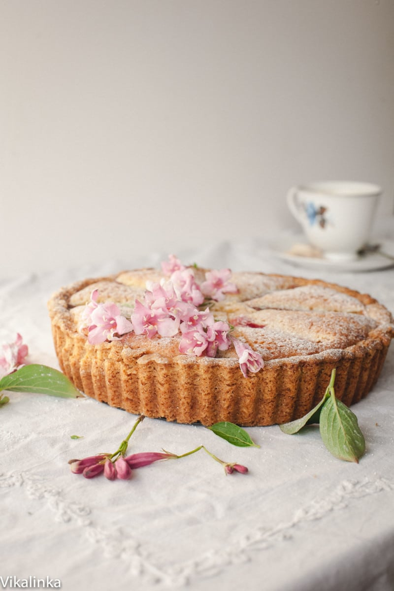 Bakewell tart decorated with pink flowers on a table covered with white tablecloth