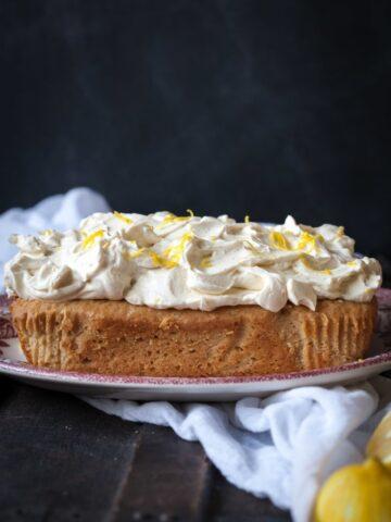 Side view of lemon ricotta cake on a plate with lemons