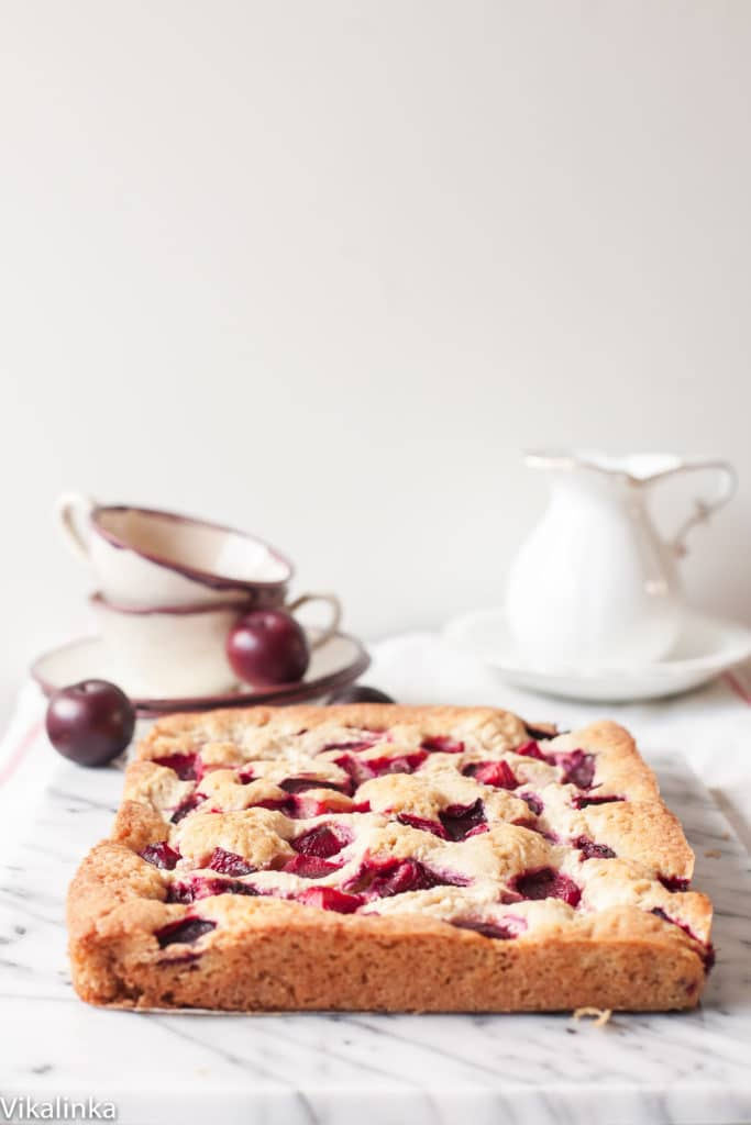 Side view of baked rustic plum cheesecake with tea set in the background