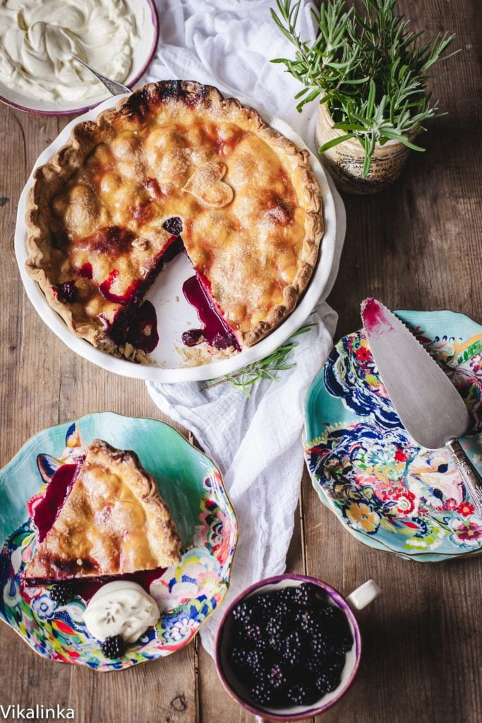 Top down view of blackberry pie with a piece cut out and on a separate plate