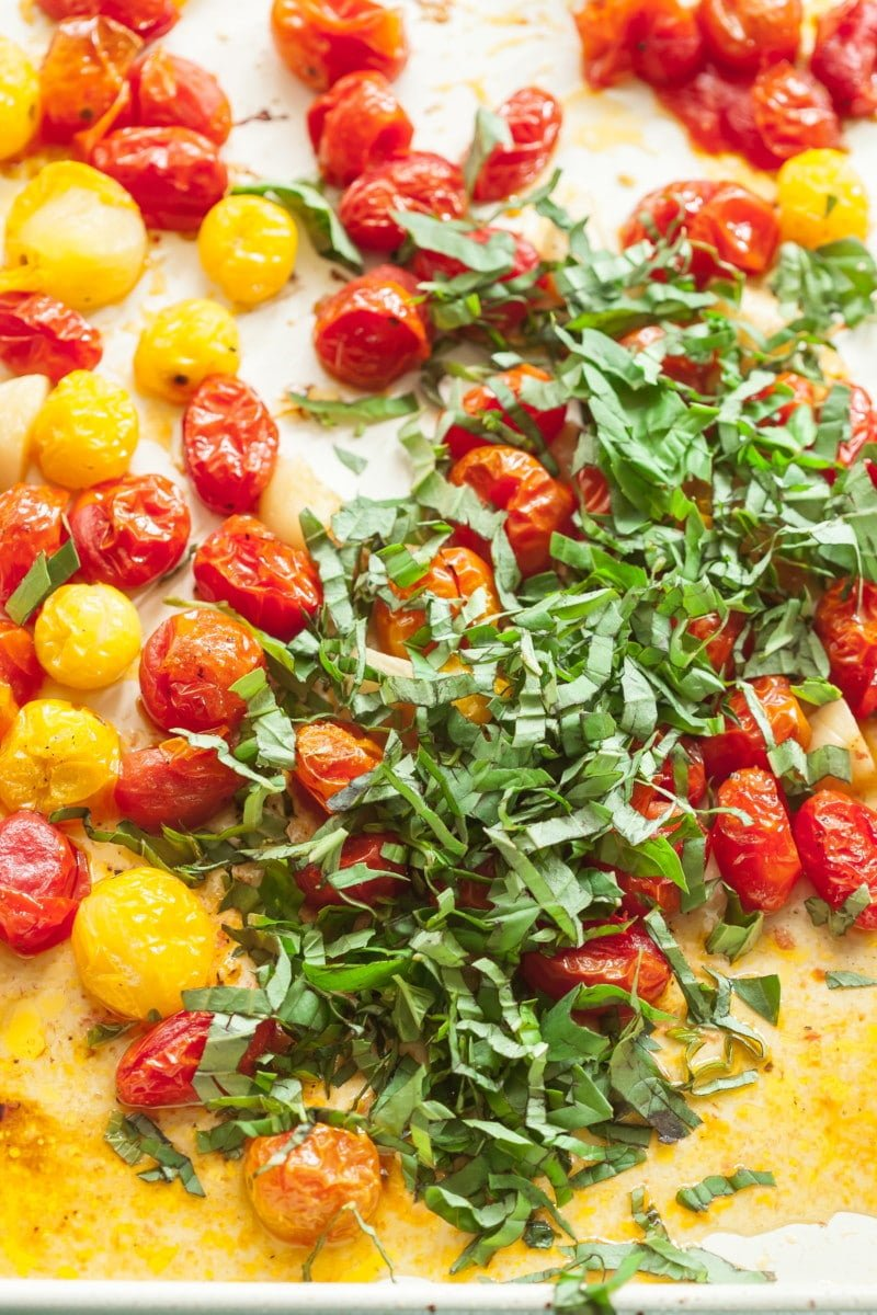 roasted cherry tomatoes on a pan topped with fresh sliced basil