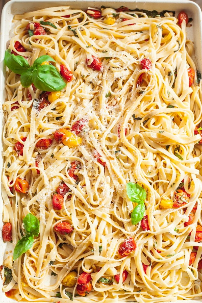 Tagliatelle tossed with roasted cherry tomato and basil sauce on a rectangular pan