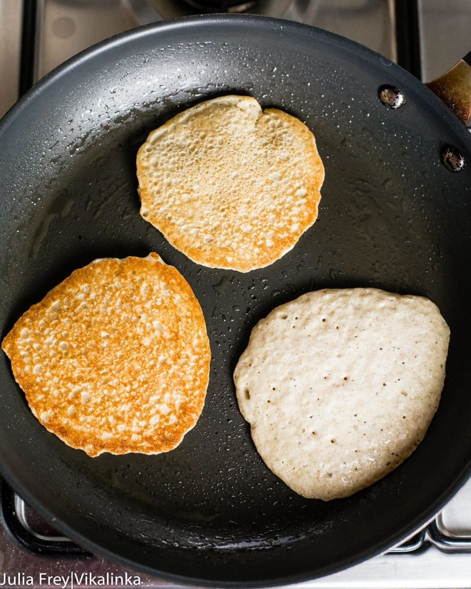 oat pancakes in a pan being cooked