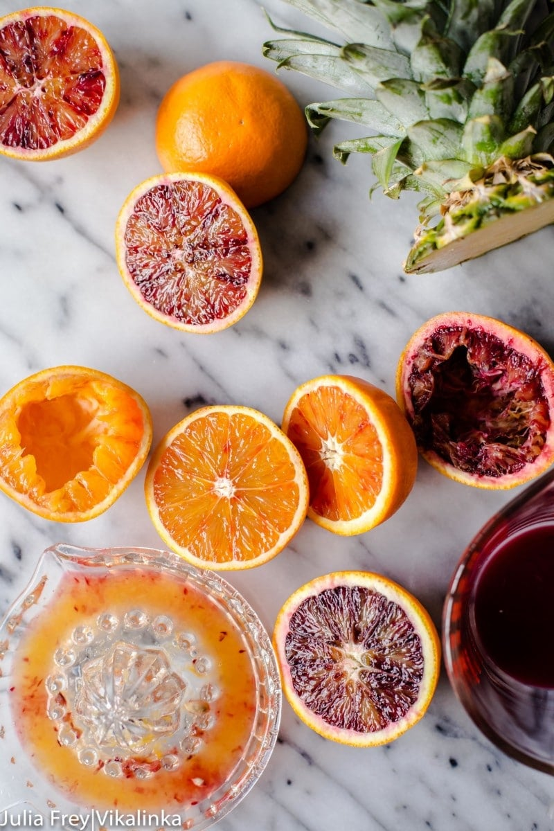 orange and blood oranges cut in half, a juice and a cut pineapple