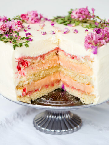 layer cake with a slice cut our exposing vanilla sponge and rhubarb curd filling