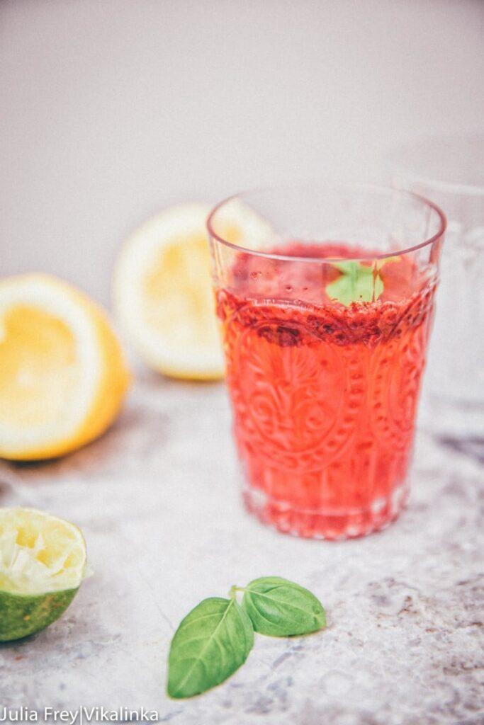 Side view of blackberry basil lemonade in a clear glasss