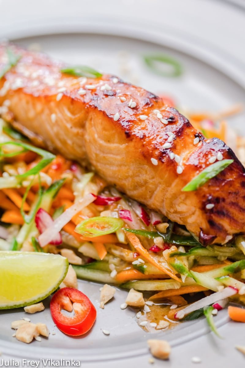 Asian glazed salmon on top of carrot and cucumber slaw with chillies.