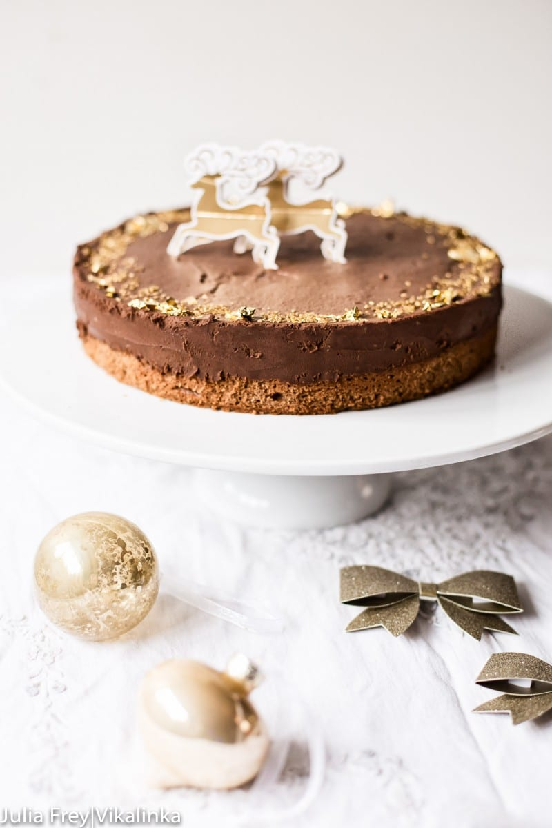 chocolate truffle cake decorated with edible gold leaf on white cake stand