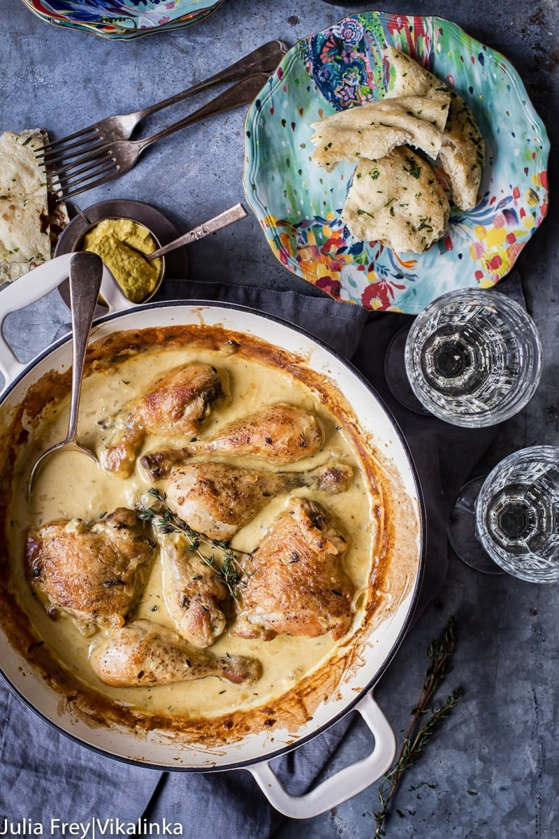 chicken in sauce in white pan, two wine glasses and a plate with torn bread pieces.