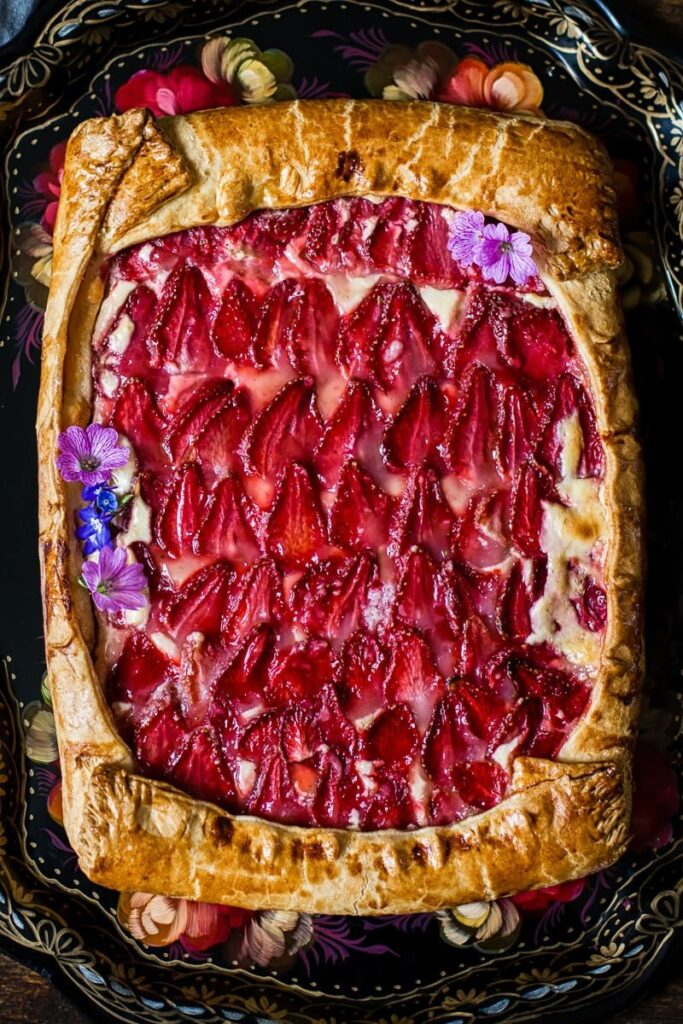 View of strawberry galette with pink flowers as decoration