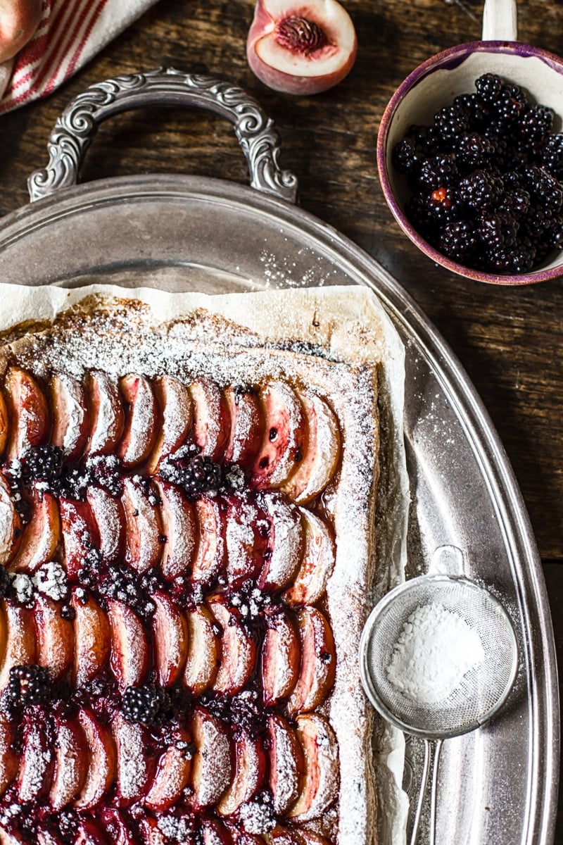 Corner of the tart next to icing sugar and blackberries